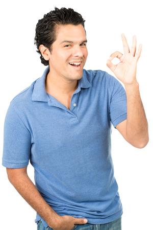 Spaanse mannelijke dragen casual kleding, het blauw shirt lacht hartelijk, blijkt OK linkerhand teken uiten van goede kwaliteit, positiviteit, tevreden tevredenheid, goedkeuring terwijl direct kijken naar de camera