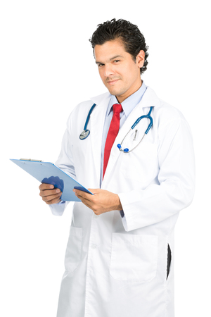 head tilted: A smiling, compassionate male latino doctor in white lab coat looking at camera, head tilted, listening and holding medical charts displaying empathy and compassion Stock Photo