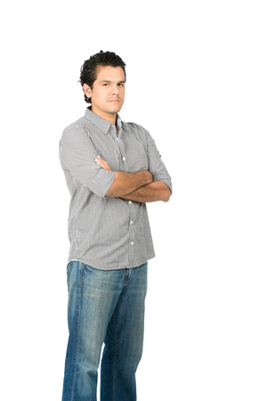 human arms: Profile of critical, judgmental hispanic man in casual clothes with arms crossed looking at camera expressing stoic, harsh, unhappy, disappointed attitude. Vertical