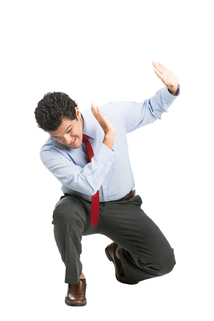 defensive posture: A frightened hispanic male office worker in business clothes