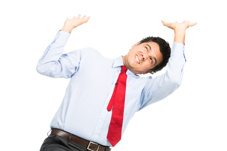 defensive posture: A struggling hispanic office worker in business clothes using arms pushing up, resisting against crushing weight, object under heavy stress, feeling pressure. Isolated on white background Stock Photo