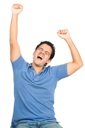 touchdown: Good looking latino man in blue casual clothes, eyes closed, celebrating a winning team or goal or event by raising arms and pumping fists expressing ecstasy, happiness, winning