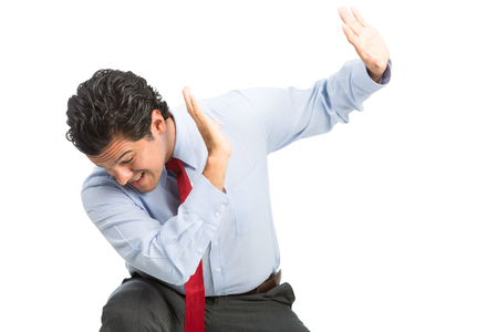 A male hispanic victim white collar office worker protecting himself with hands up in defensive position from workplace physical, verbal abuse, violence. Horizontal