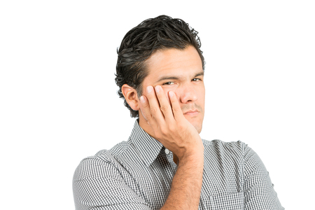 consternation: Portrait of concerned, worried hispanic male in casual clothes cupping face in hand looking at camera, thinking with deep consternation, alarm, dismay