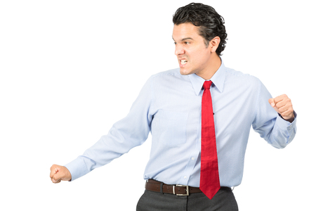 fighting arts: An aggressive hispanic male business professional in formal dress shirt, red tie, fierce facial expression strikes a martial arts kung fu pose looking away to side fighting opponent. Half