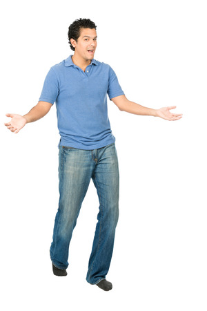 Handsome hispanic man in casual clothes, socks, no shoes, both hands, arms out to side, presenting himself, surprise in tada body language gesture while looking at camera Banque d'images