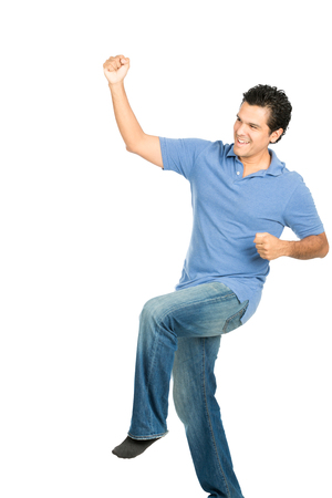 fist pump: Happy smiling good looking hispanic male in casual clothes, no shoes celebrating indoors with victorious fist pump into the air looking away from camera Stock Photo