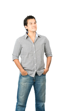 A curious, reserved latino man in casual clothes looking up away from camera with curiosity at empty copy space or product placement showing wonder, interest, or pensive thought