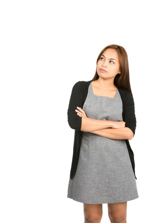 standing up: A pensive Asian woman wearing dress, sweater with serious, curious expression, arms crossed thinking, looking up to side at copy space with thought, wonder. Thai national of Chinese origin. Vertical