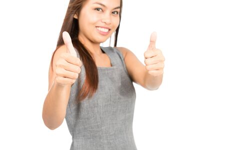 two thumbs up: A cute Asian woman in sleeveless gray dress approving with two thumbs up, focus on thumbs which a job well done, agreement, compliment or endorsement. Thai national of Chinese origin Stock Photo