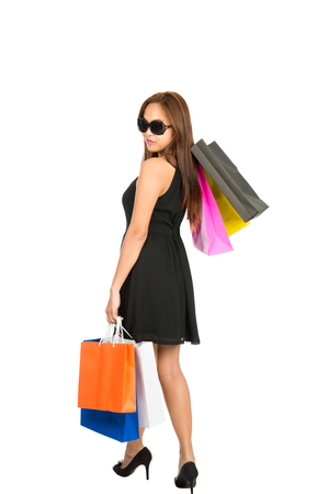 looking away from camera: The rear of a beautiful Asian female shopper wearing a black elegant dress walking away with colorful shopping bags at side and slung over looking back over her shoulder. Isolated white full length