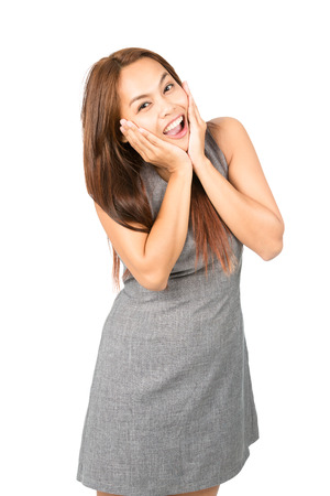 reacting: A thrilled, euphoric Asian woman, light brown hair in gray dress, chin cupped, head in hands reacting blissfully to happy news or results. Thai national of Chinese origin. Half