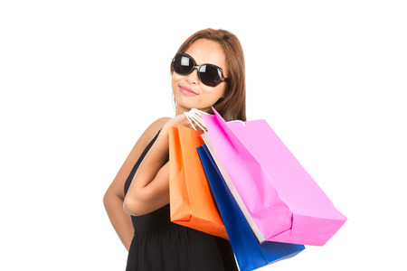 half length: A cute sassy Asian girl with sunglasses smiles, carrying colorful department store shopping bags flung over shoulder facing camera. Half length isolated on white. Thai national of Chinese origin