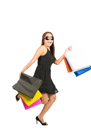 frantic: A stylish Asian woman shopper wearing a stylish black dress and sunglasses runs with energy, excitement in a hurry with department store shopping bags and a big smile showing frantic ecstatic energy Stock Photo