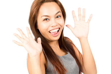 two hands: Portrait of cute, youthful Asian girl with light brown hair looking at camera with two hands up waving is pleasantly surprised and happy to see a friend. Thai national of Chinese origin Stock Photo