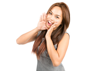 announcing: Portrait of lovely Asian girl, sleeveless gray dress, light brown hair looking at camera, announcing cupping hands around mouth amplifying sound. Thai national Chinese origin. Half length Horizontal