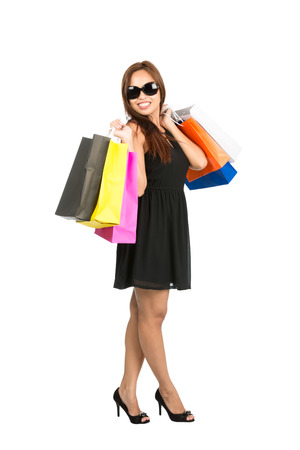 Full body isolated on white profile of classy Asian female shopper, shopaholic in black dress and sunglasses flinging shopping bags over her shoulders ready to shop while looking at the camera Banco de Imagens