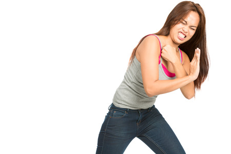 product placement: Struggling Asian woman clenched teeth pained face in casual clothes leaning, driving back and pushing against inserted object or product placement coming from side using body weight. Horizontal