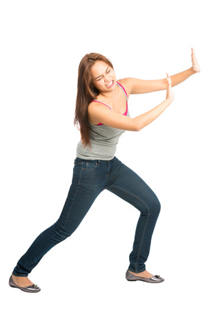 product placement: Full length isolated on white background of Asian woman in casual clothes with extended arms open palms, struggling, forcing, leaning, pushing against imaginary product placement object. Copy Space