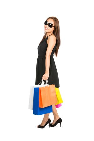 casually: Isolated on white background profile of an attractive female shopper casually standing around wearing a stylish black dress and sunglasses holding colorful shopping bags. Full length