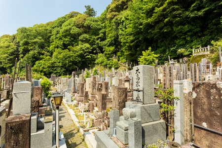 graves: Old graves and headstones of the deceased at a Buddhist cemetery upstairs and behind Chion-In temple in ancient Kyoto, Japan. Horizontal