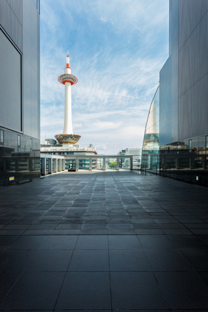 neighboring: A blue sky with wispy clouds behind Kyoto Tower at daytime framed by modern lines and walls of a neighboring building balcony
