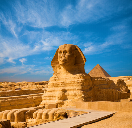 pyramid egypt: Full length body profile of Great Sphinx including head, feet with great pyramid of Menkaure in background on a clear, blue sky day in Giza, Egypt empty with no people. Copy space