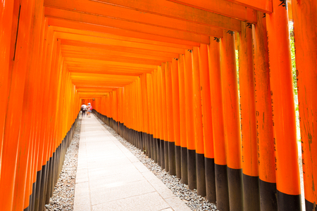 vanishing point: Tourists walking inside the end vanishing point of the repetitive red painted torii gates with black base at the beautiful Fushimi Inari Taisha Shrine in Kyoto, Japan. Horizontal copy space Editorial