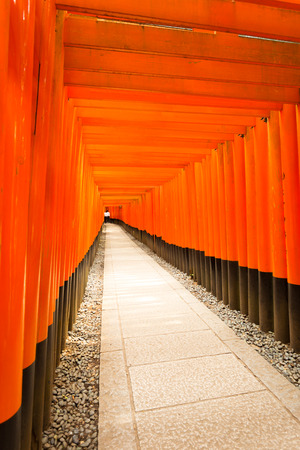 vanishing point: Unidentified students inside the far end of vanishing point repeating red torii gates and stone footpath at Fushimi Inari Taisha Shrine in Kyoto, Japan. Vertical copy space