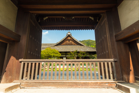 centered: A large main gate front entrance frames the centered exterior of ancient Shoren-In Temple on a sunny day in Kyoto, Japan. Horizontal Editorial