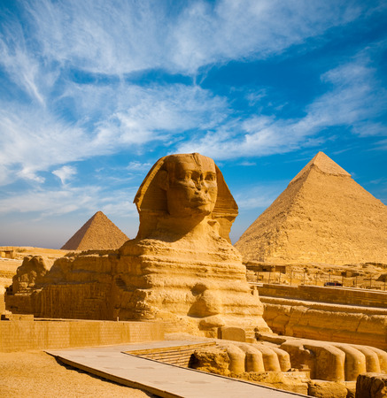 egyptian pyramids: Full profile of Great Sphinx including pyramids of Menkaure and Khafre in the background on a clear sunny, blue sky day in Giza, Cairo, Egypt with no people