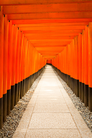 centered: Centered stone walkway leads straight down the middle of repeating symmetrical red torii gates at Fushimi Inari Shrine during daytime with nobody present in Kyoto, Japan. Vertical copy space