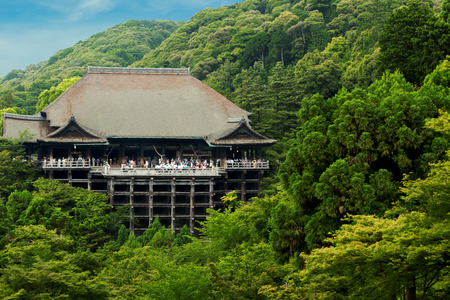 dera: Distant view of Kiyomizu-dera temple nestled in green forest crowded with throngs of tourist visitors on a clear blue sky day in Kyoto, Japan Editorial