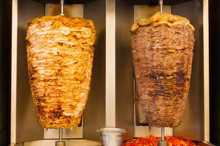 Heerlijke platen van doorstoken fast food shawerma kip en lamsvlees zijn beurt naast elkaar op een spit. Dit is gebruikelijk sandwich vlees gevonden in fast food in het Midden-Oosten.