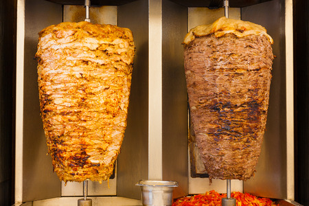 Delicious slabs of skewered fast food shawerma chicken and lamb meat turn side by side on a spit. This is common sandwich meat found in fast food in the Middle East.