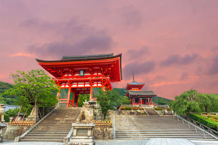 main gate: Beautiful fiery sunset sky behind Ro Mon and Triple Pagoda at the stairs entrance to Kiyomizu-dera Temple in the evening with no people present in Kyoto, Japan. Horizontal copy space