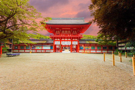centered: Front entrance tower gate and open door to Shimogamo Shrine, centered and symmetrical, formally known as Kamo Mioya Jinja, one of the oldest shrines in Kyoto, Japan at evening sunset