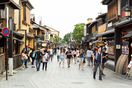 entertainment district: KYOTO, JAPAN - JUNE 15, 2015: Tourists walking down Hanami-Koji dori, the street at the heart of Gion and its famous Geisha entertainment district lined with ancient teahouses and restaurants