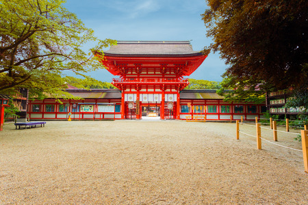 centered: Clear blue sky at front entrance tower gate and open door to Shimogamo Shrine, centered, formally known as Kamo Mioya Jinja, one of the oldest shrines in Kyoto, Japan during daytime showers