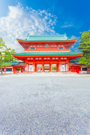 centered: Front centered view of large red front Tower Gate Ro-Mon at the chinowa-kuguri decorated entrance of Heian Jingu Shrine on a clear, blue sky day in Kyoto, Japan. Vertical