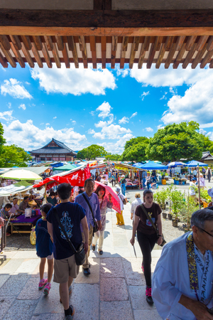 KYOTO, JAPAN - JUNE 21, 2015: People shopping at outdoor stalls of the once a month Toji market on the grounds of the temple. Vertical