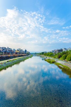 leisurely: KYOTO, JAPAN - JUNE 20, 2015: People leisurely resting and restaurants line the banks of the Kamo River on a late afternoon on a blue sky day in central Kyoto. Vertical Editorial