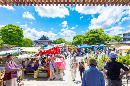 KYOTO, JAPAN - JUNE 21, 2015: People shopping at outdoor stalls of the once a month Toji market on the grounds of the temple. Horizontal