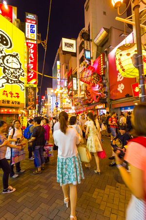 overwhelming: OSAKA, JAPAN - JUNE 23, 2015: Tourists walking around crowded and busy Dotombori Arcade amid bright neon signs and lights, the center of nightlife at night in Minami area of Osaka, Japan. Vertical Editorial