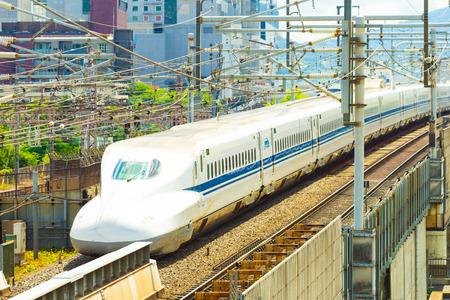 KYOTO, JAPON - 21 juin 2015: la queue d'un départ de train Shinkansen de balle haute vitesse laissant Kyoto au milieu des fils et des bâtiments en vue de dessus