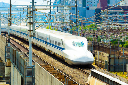 above 21: KYOTO, JAPAN - JUNE 21, 2015: Approaching Shinkansen bullet train on high elevated rails surrounded by wires seen from above aerial view leaving city of Kyoto, Japan. Horizontal