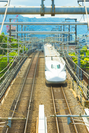centered: KYOTO, JAPAN - JUNE 21, 2015: Front of high bullet train approaching directly head on with two railroad tracks centered and symmetrical seen from above
