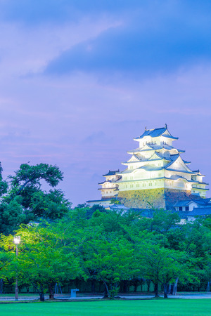 lighted: Himeji-jo castle lighted at evening sunset with deep purple sky and foreground trees from nearby park in Himeji, Japan after 2015 completely renovated. Vertical copy space Editorial