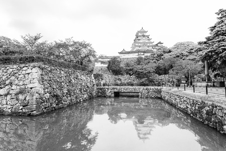 rampart: Himeji-jo castle reflection in green water of the surrounding moat and rampart wall during overcast day in Himeji, Japan after 2015 renovations finished. Horizontal black and white Stock Photo