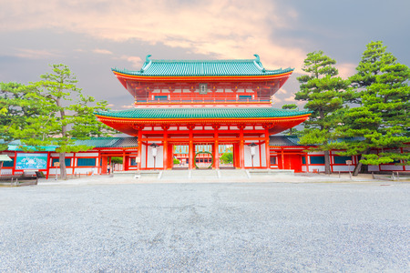 centered: A brightly colored evening sunset sky behind the centered large red main Tower Gate Ro-Mon at the chinowa-kuguri decorated front entrance of Heian-Jingu Shinto Shrine in Kyoto, Japan. Horizontal